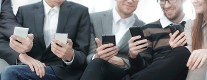 Cierre para arriba el equipo del negocio utiliza sus smartphones fotos de archivo libres de regalías
