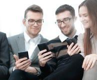 Cierre para arriba el equipo del negocio utiliza sus smartphones foto de archivo libre de regalías