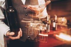 Cierre para arriba El Sommelier en corbata de lazo se está sosteniendo con la botella de vino y de copa de vino enmascarado fotos de archivo