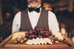 Cierre para arriba El Sommelier está sosteniendo los bocados para el vino rojo en la placa de madera Uvas Queso Aceitunas nuez fotos de archivo libres de regalías