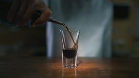 Cierre para arriba el vídeo de verter el licor oscuro al vidrio en el alcohol a cámara lenta, de colada en una barra, camarero en almacen de metraje de vídeo
