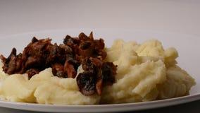 Cierre para arriba En los purés de patata, ponga una espátula del tocino frito con las cebollas y las setas metrajes