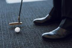 Cierre para arriba Golf de la oficina Club de golf y pelota de golf en una alfombra gris Fotos de archivo libres de regalías