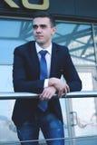 Cierre para arriba hombre de negocios joven que se coloca en balcón en oficina Foto de archivo libre de regalías