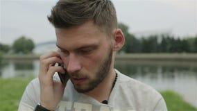 Cierre para arriba Hombre joven atractivo con la barba que se sienta en un banco del río y que habla en el teléfono móvil almacen de video