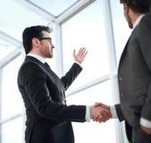 Cierre para arriba hombres de negocios que sacuden las manos durante una conversación en la oficina fotos de archivo libres de regalías