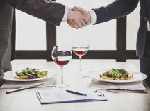 Cierre para arriba Hombres de negocios que sacuden las manos en restaurante Foto de archivo