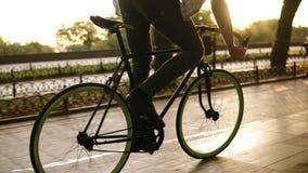 Cierre para arriba la cantidad de las piernas masculinas que completan un ciclo una bicicleta en el parque o el bulevar de la mañ metrajes