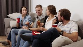 Cierre para arriba la cantidad de los buenos amigos que cuelgan hacia fuera junto dentro Sentándose en el sofá, bebiendo, comiend almacen de video