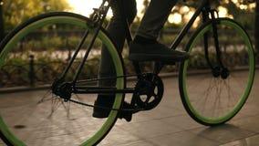 Cierre para arriba la cantidad de los pies masculinos que completan un ciclo una bicicleta en el parque de la mañana por el camin almacen de video