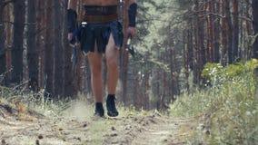 Cierre para arriba la cantidad de un guerrero en la ropa de cuero con dos hachas a disposición que camina almacen de video
