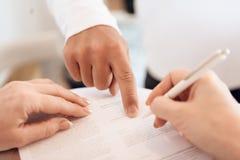 Cierre para arriba La mano masculina dura señala con el finger donde poner la firma en el documento fotos de archivo