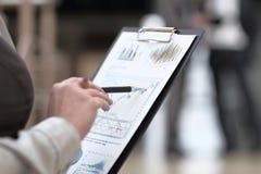 Cierre para arriba la mujer de negocios comprueba el informe financiero imagenes de archivo