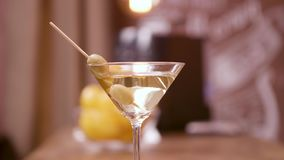 Cierre para arriba la paralaje tirada de un vidrio de martini adornado con las aceitunas almacen de metraje de vídeo