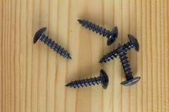 Cierre para arriba la textura de la pila negra de los tornillos de metal, tornillos negros del hierro en una tabla de madera foto de archivo