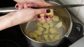 Cierre para arriba Las manos de las mujeres cortaron las patatas en un pote metrajes