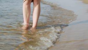 Cierre para arriba Las piernas femeninas atractivas caminan en el mar almacen de metraje de vídeo