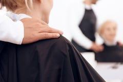 Cierre para arriba Mano de la mentira del estilista en el hombro de la mujer que se sienta en butaca del ` s del peluquero foto de archivo
