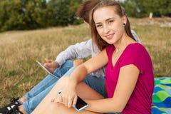 Cierre para arriba Muchacha feliz joven que sostiene el teléfono móvil en parque En Imagenes de archivo