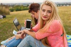 Cierre para arriba Muchacha feliz joven que sostiene el teléfono móvil en parque En Foto de archivo
