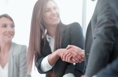Cierre para arriba mujer de negocios sonriente que sacude las manos con los socios foto de archivo libre de regalías