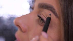 Cierre para arriba Ojos, cejas La muchacha pinta una forma de la ceja con un lápiz 4K MES lento almacen de video