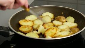 Cierre para arriba Patatas en un sartén frito en mantequilla La mano de una mujer da la vuelta a los pedazos con un cuchillo Conc metrajes