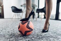 Cierre para arriba Pies femeninos de primer Una pierna se coloca en un balón de fútbol anaranjado En un fondo de la oficina Imagenes de archivo