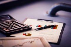 Cierre para arriba pluma oro-inclinada y carta financiera en la tabla fotografía de archivo