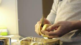 Cierre para arriba Sirva las patatas de la peladura de la mano del ` s con el cuchillo almacen de video