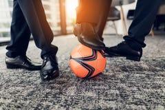 Cierre para arriba Tres hombres en pantalones estrictos y zapatos negros juegan una bola anaranjada en fútbol en la oficina Imágenes de archivo libres de regalías