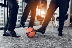 Cierre para arriba Tres hombres en pantalones estrictos y zapatos negros juegan una bola anaranjada en fútbol en la oficina Foto de archivo libre de regalías