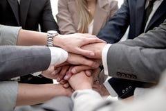 Cierre para arriba un equipo enfocado del negocio que pone sus manos juntas imagenes de archivo