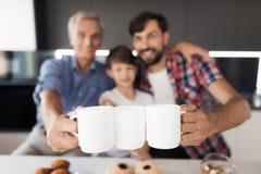 Cierre para arriba Un muchacho, un hombre y un viejo hombre están presentando con las tazas de té en la cocina Están sonriendo imágenes de archivo libres de regalías