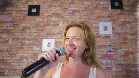 Cierre para arriba una mujer que grita a un micrófono una mujer canta Karaoke en un micrófono en un ajuste casero 4k, cámara lent almacen de metraje de vídeo