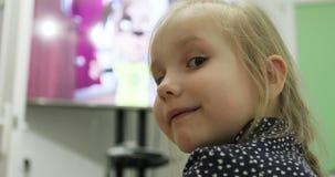 Cierre para arriba Visión posterior La pequeña muchacha rubia mira la historieta en la TV y da vuelta detrás almacen de metraje de vídeo