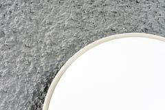 Cierre redondo de la luz de la lámpara para arriba con la opinión gris del extracto de la pared Foto de archivo