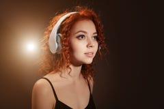 Cierre rizado del retrato de la muchacha del pelirrojo hermoso para arriba con los auriculares Imágenes de archivo libres de regalías