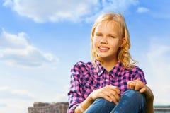 Cierre rizado rubio de la muchacha encima de la sentada de la visión Imagen de archivo libre de regalías