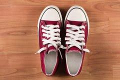 Cierre rojo de la opinión superior de las zapatillas de deporte para arriba en fondo de madera Foto de archivo libre de regalías
