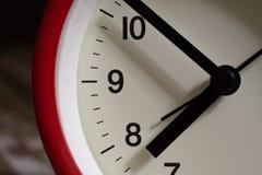 Cierre rojo del despertador para arriba It' s que muestra diez minutos a ocho o' cl Imágenes de archivo libres de regalías