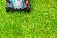 Cierre sin cuerda del cortacésped del poder de batería para arriba en backgr de la hierba verde foto de archivo libre de regalías
