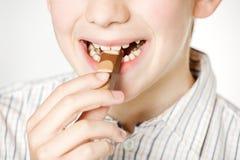 Cierre sonriente de la barra del chocolate con leche de la consumición del muchacho para arriba Foto de archivo