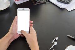 Cierre suave del foco encima de la mano del hombre usando Smartphone en usin del hombre del café Fotos de archivo libres de regalías