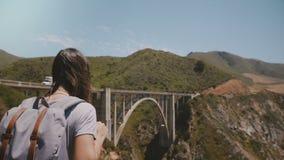 Cierre trasero de la visión encima del tiro de la mujer joven del viajero con la mochila que camina al punto increíble del vista  almacen de metraje de vídeo
