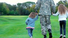 Cierre trasero de la visión encima de la familia feliz con el padre militar almacen de video