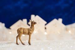 Ciervos de la Feliz Navidad del invierno en la ciudad de la nieve imagenes de archivo