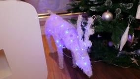 Ciervos de la Navidad que brillan intensamente cerca de un árbol de navidad metrajes