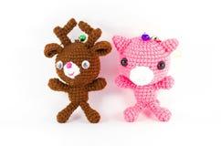 Ciervos hechos a mano del marrón del ganchillo y muñeca rosada del cerdo en el backgroun blanco Imágenes de archivo libres de regalías