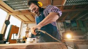 Ciesielka z męskiego pracownika polerowniczym drewnem mechanically Rzemieślnik pracuje w ciesielce zbiory
